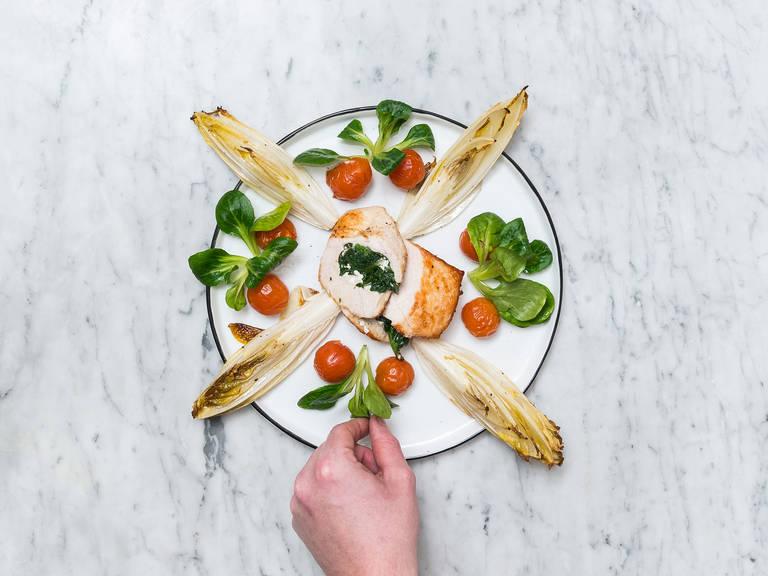 Feldsalat waschen. Gefüllte Hähnchenbrust mit geröstetem Chicorée, Cherrytomaten und Feldsalat servieren. Guten Appetit!