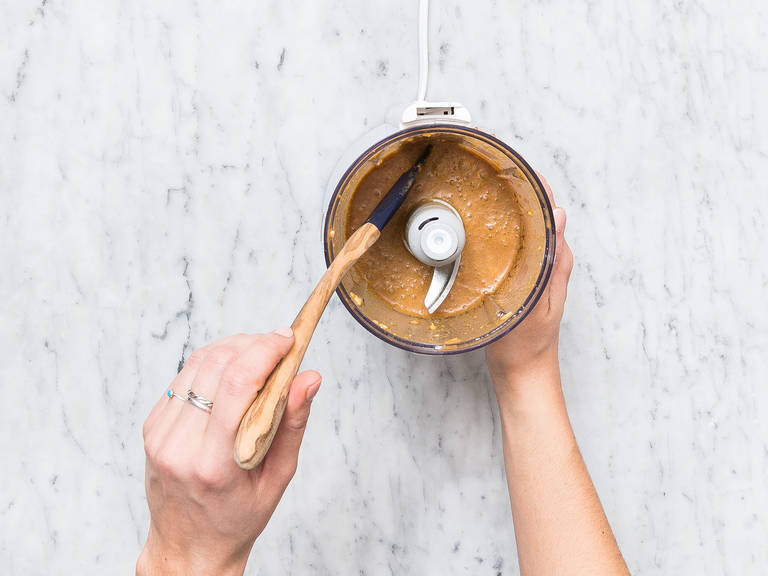 Ingwer und Knoblauch schälen und zusammen mit roter Currypaste, Saft von der Hälfte der Limette, Kokosmilch, Sojasauce und Honig in einen Zerkleinerer geben. Zu einer cremigen Soße vermengen. Die restliche Limette zum Servieren in Spalten schneiden und beiseitelegen. Koriander waschen, grob hacken und ebenfalls beiseitelegen.