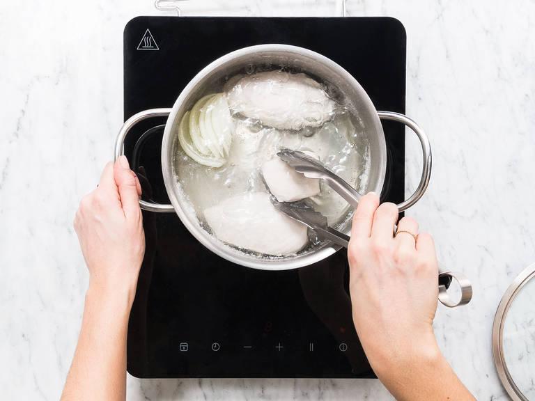 Einen Topf mit Wasser füllen und über hoher Hitze zum Kochen bringen. Einen Teil der Zwiebel und des Knoblauchs schälen und ins kochende Wasser geben. Großzügig mit einer Handvoll Salz würzen. Hähnchenbrust dazugeben und über mittlerer Hitze ca. 20 Min. pochieren, bis das Fleisch gar ist. Anschließend die Hähnchenbrust in eine Schüssel geben und abkühlen lassen. Mit zwei Gabeln in Stücke zupfen und beiseitestellen.