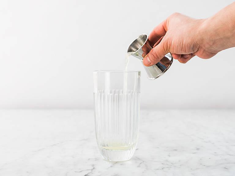 Zitronensaft und Wodka in ein Longdrinkglas füllen. Zitronenzeste über dem Glas ausdrücken und mit Eiswürfeln ins Glas geben.