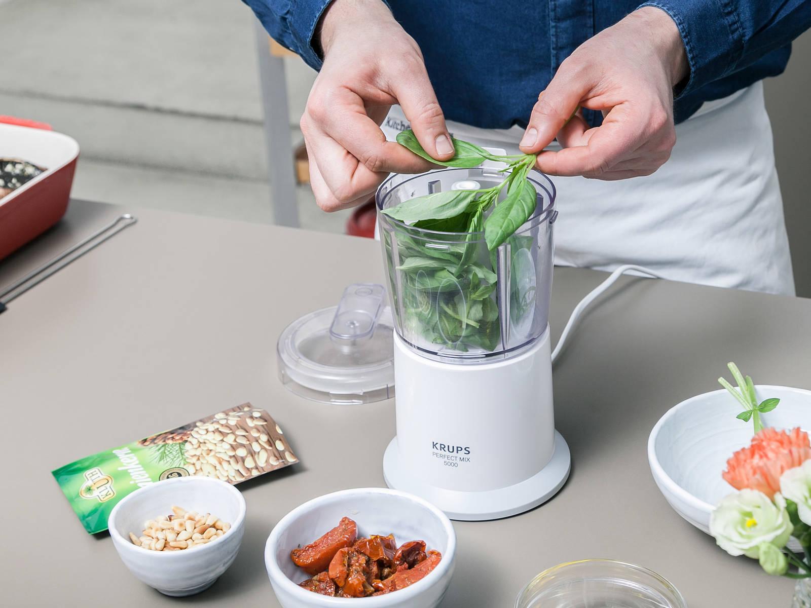 与此同时,将松仁放到平底锅里烘一烘,然后倒出至一只碗中。摘下罗勒叶片,放到料理机中。再加入干番茄、烤松子、部分橄榄油、盐与胡椒,搅打成酱料,置于一旁。