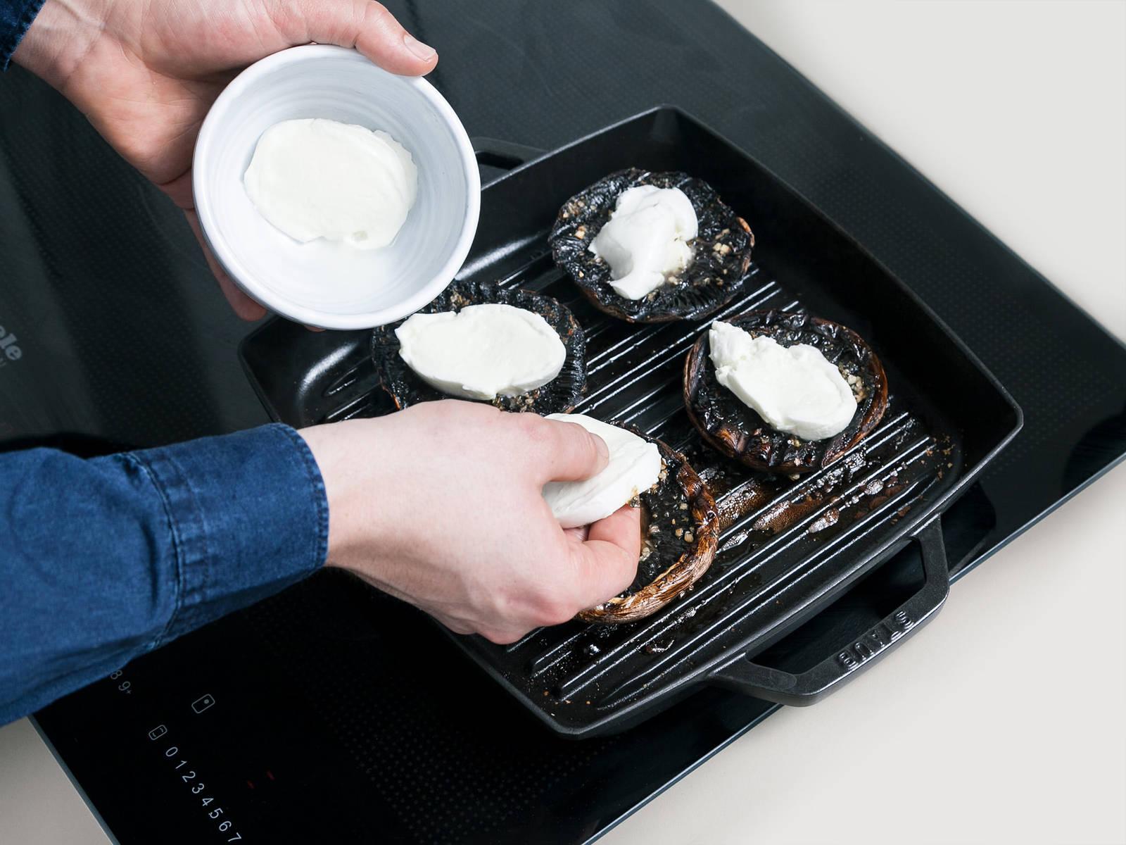 中高火加热烧烤平底锅,烤汉堡面包。烤好后置于一旁待用。将蘑菇带皮一面朝上地放入锅中,煎烤2分钟。翻面,放上马苏里拉奶酪片,再煎2分钟。