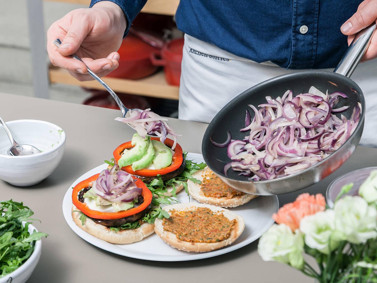 将酱料抹在两片汉堡面包夹放食材的一面。在一个面包上放芦笋、波特菇和马苏里拉奶酪、甜椒圈、牛油果片和洋葱,盖上另一个面包,尽情享用吧!