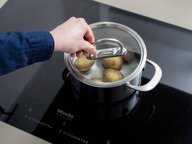 Wasser in einem Topf zum Kochen bringen. Salz und Frühkartoffeln in den Topf geben und für ca. 10 Min. kochen. Abgießen und Kartoffeln pellen, beiseitestellen und abkühlen lassen.