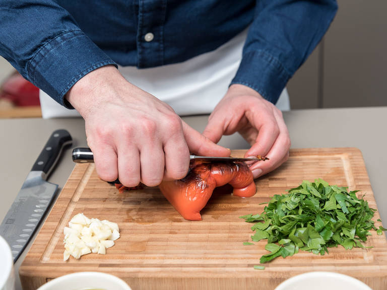 Preheat the oven to 250°C/480°F. Halve and deseed the red bell pepper. Transfer to a baking dish cut side down and bake on the top shelf of the preheated oven for approx. 15 min. or until skin is blistered all over. Meanwhile, chop parsley, crush and chop some of the garlic cloves. Transfer blistered pepper to a bowl and cover with plastic wrap. Let rest for approx. 15 min. then use a small knife to peel the pepper. Discard the skins and thinly slice the pepper. Transfer to a bowl and season with salt, pepper, crushed garlic cloves, chopped parsley, and olive oil. Cover the bowl with plastic wrap and let marinate at room temperature overnight.