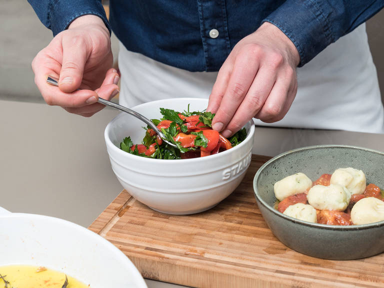 Meanwhile, chop some of the confit tomatoes and transfer to a serving dish with some of the roasting oil. Using a slotted spoon, transfer the gnocchi to a serving dish with the tomatoes. Top with marinated red pepper and parsley mixture. Enjoy!