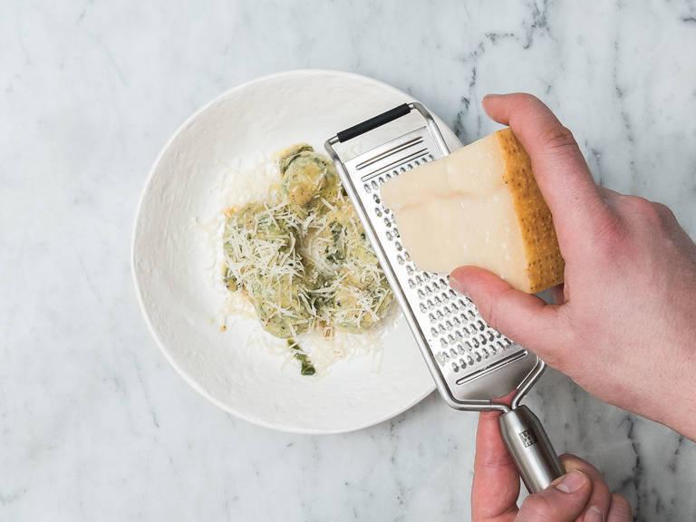 Die fertig gegarten Gnudi mit einer Schaumkelle aus dem Wasser nehmen und zur Butter-Soße in die Pfanne geben. Hitze reduzieren und die Pfanne vorsichtig schwenken, um die Gnudi mit der Soße zu bedecken. Mit frisch geriebenem Parmesankäse sofort servieren, nach Wunsch abschmecken und genießen!