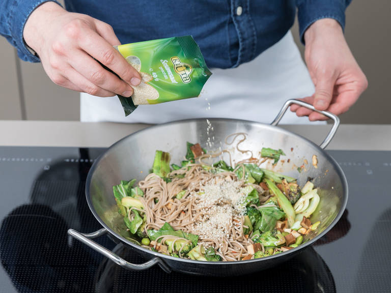 Add soba noodles to the wok and toss gently to coat with the sauce. Season with salt and pepper, and top with sesame seeds. Enjoy!
