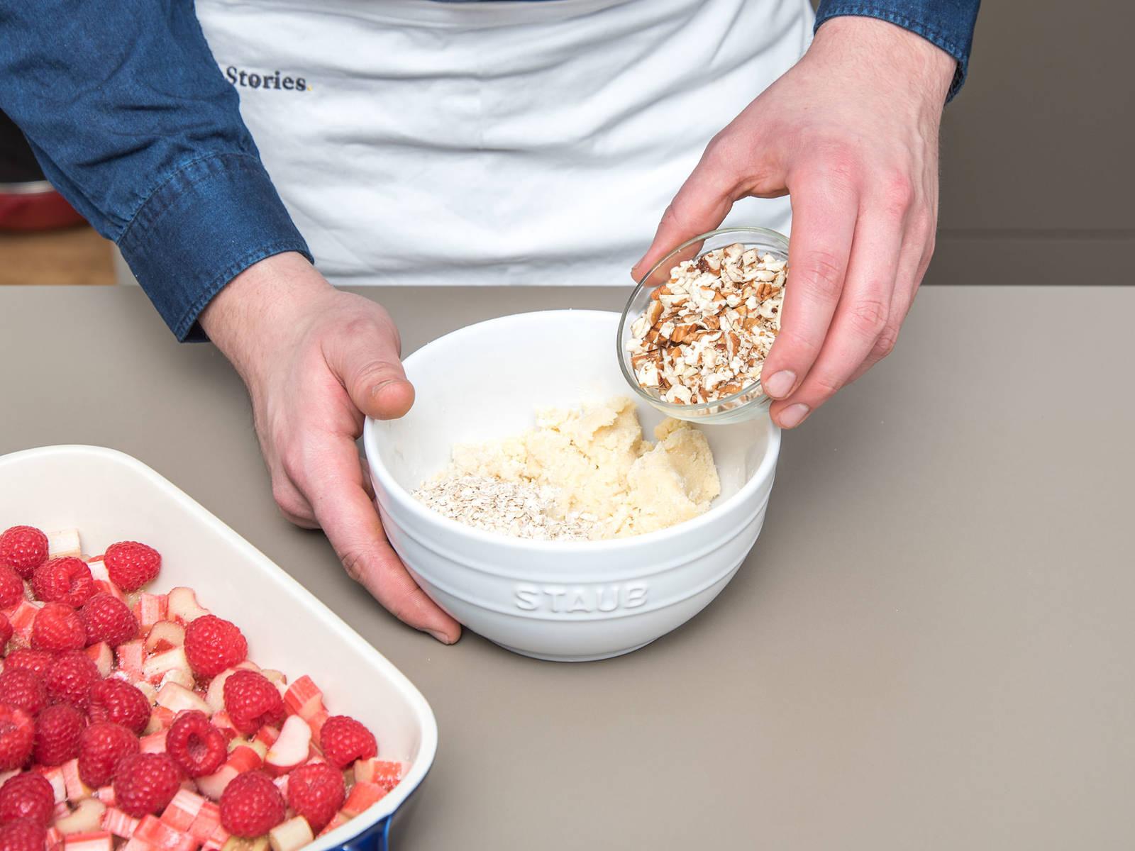 烤箱预热至190°C(环绕式)。黄油切小块,和剩余的糖和面粉混合,用指尖揉搓成酥粒面团。大略切碎碧根果,和燕麦片与酥粒面团混合。