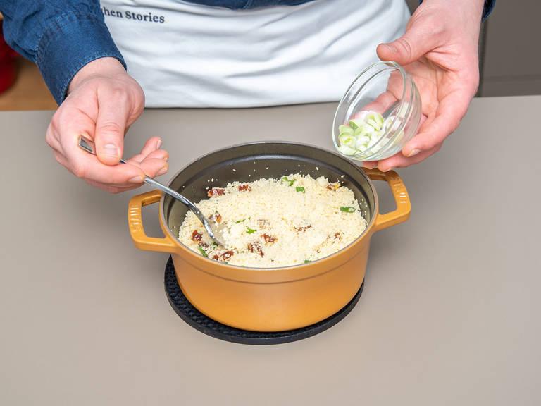 Den Couscous mit einer Gabel auflockern. Klein geschnittene Datteln, restliche Petersilie und Frühlingszwiebeln untermischen.
