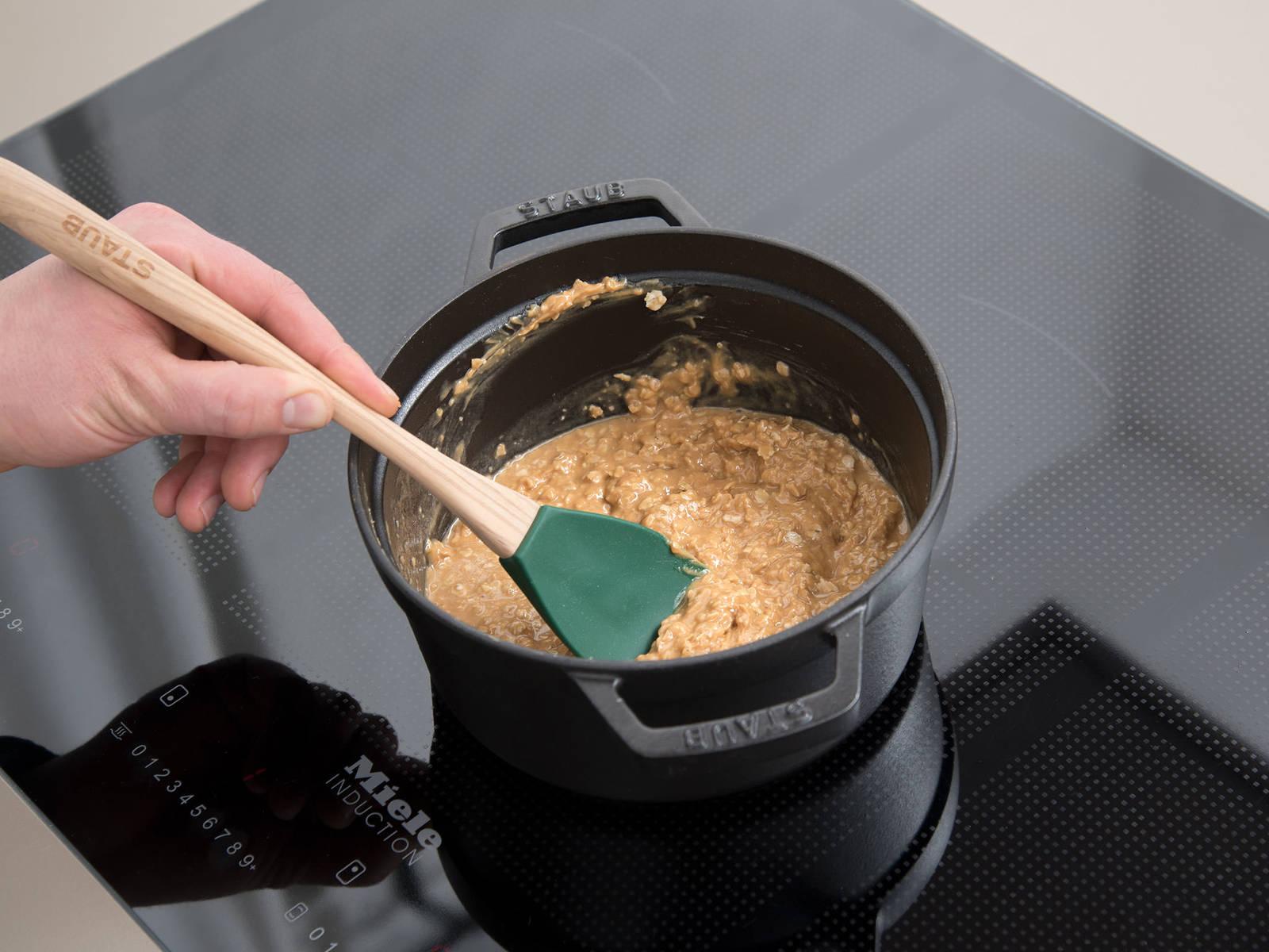 Erdnussbutter, Ahornsirup und Haferflocken in einer Schüssel mit einem Gummispatel vermengen. Kokosöl in einem kleinen Topf schmelzen, die Erdnussbutter-Mischung dazugeben und ca. 1 Min. köcheln.