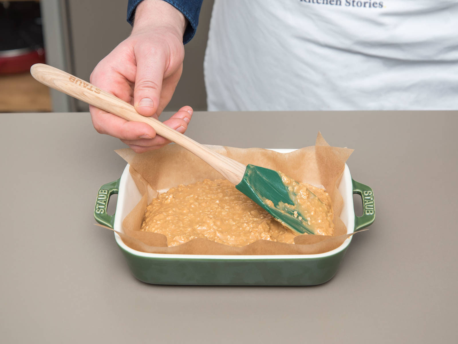 Line the baking dish with parchment paper and spread the peanut butter oat mixture evenly into the bottom of the dish with the rubber spatula. Press firmly. Freeze for approx. 20 min.