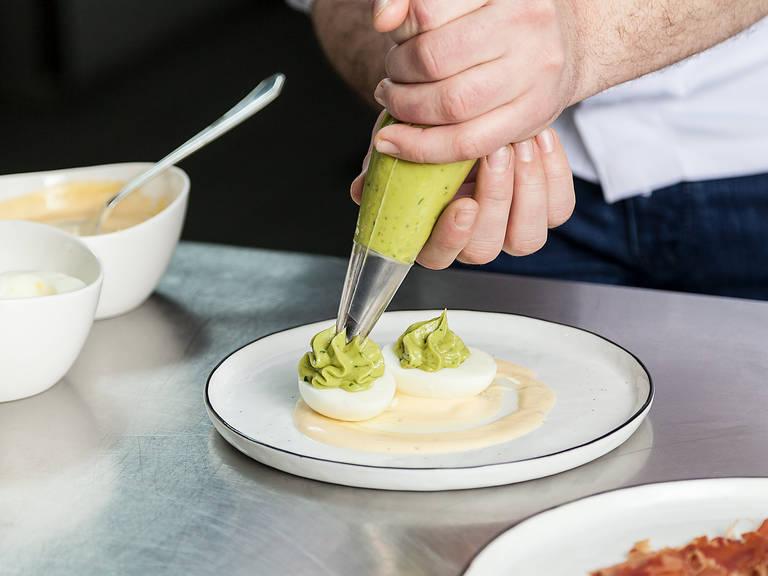 Prosciutto aus dem Backofen nehmen, vom Küchenpapier lösen und auf einen Teller geben. Petersilie hacken. Mayonnaise auf einem Teller verstreichen, die gekochten Eierhälften darauf anrichten und mit Avocadocreme füllen. Prosciutto darüber verteilen und mit Petersilie garnieren. Abschließend mit Salz und Pfeffer abschmecken. Guten Appetit!