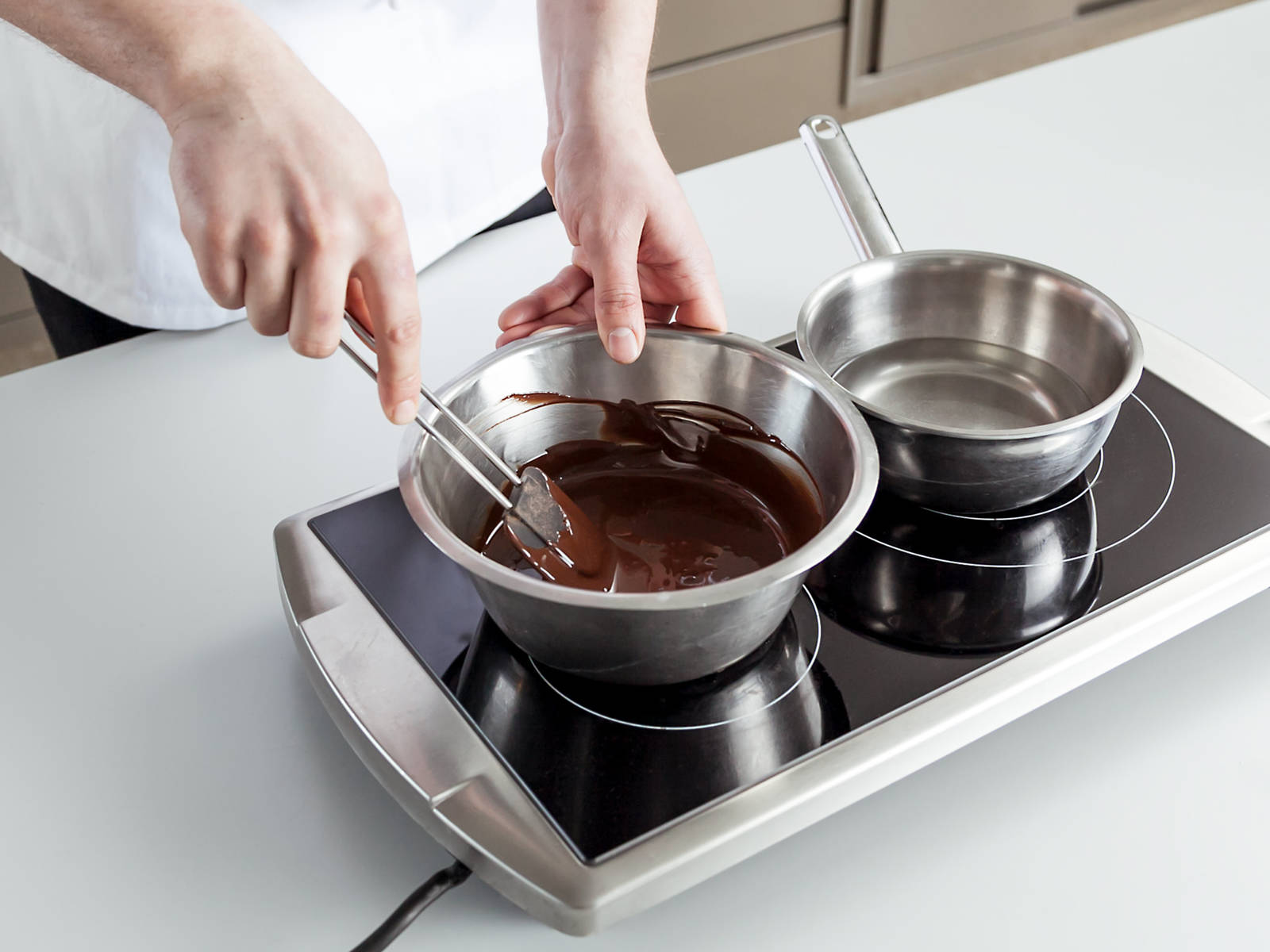 Chop dark chocolate. In a heatproof bowl, melt some of the chocolate over a saucepan filled with simmering water. Meanwhile, inflate and knot the balloons. Remove chocolate from heat and stir in the remaining chocolate until melted and smooth.