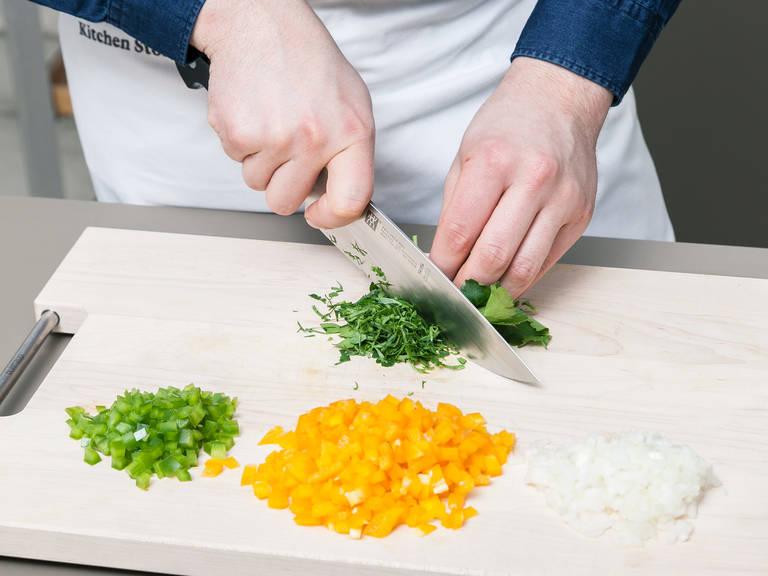 洋葱去皮剁碎。清洗红绿灯笼椒后去籽切丁。摘下欧芹叶,剁碎。