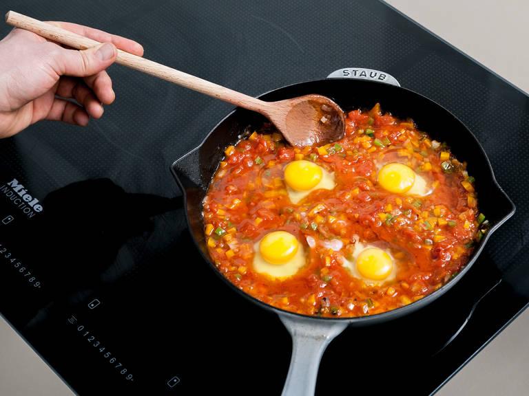 用料理勺在番茄灯笼椒混合物中间挖出四处凹陷,挨个往里打入一颗鸡蛋。加热1分钟,或直至鸡蛋稍微凝固。然后以打圈的动作将鸡蛋与混合物拌到一起,继续加热5分钟,或直至鸡蛋完全凝固。捏碎菲达芝士,撒入其中,饰以欧芹末。搭配新鲜面包享用吧!