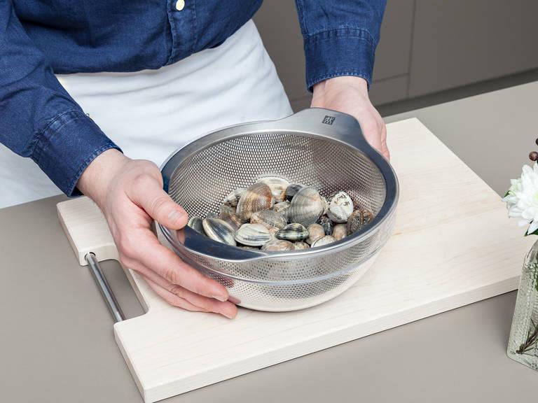 Muscheln sorgfältig waschen, dabei offene und beschädigte Exemplare aussortieren. Muscheln in eine Schüssel mit kaltem Wasser legen und ca. 1 Std. ruhen lassen. Danach durch ein Küchensieb abgießen.