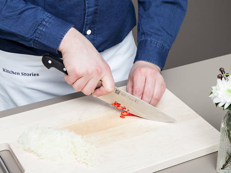 Knoblauch fein hacken und Zwiebeln würfeln. Chili längs aufschneiden, entkernen und fein schneiden.