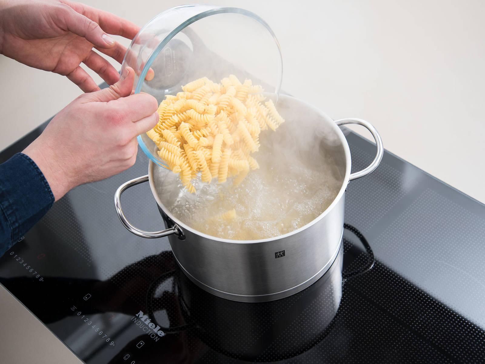 在一个锅中,煮沸适量水,加盐融化后,放入意面,煮至意面变熟且有嚼劲。与此同时,将烤箱预热至200℃。