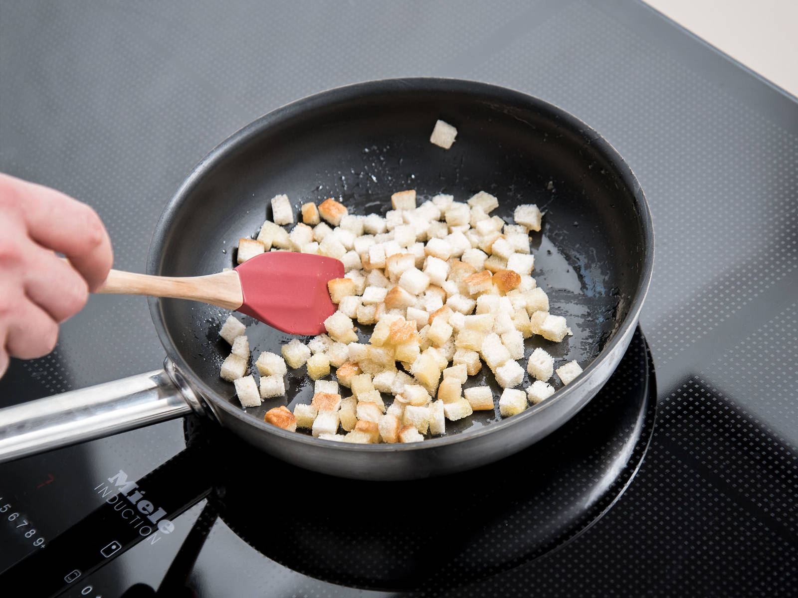 Add olive oil and butter to a frying pan set over medium-high heat. Add bread cubes and fry until golden brown. Season with salt and pepper.
