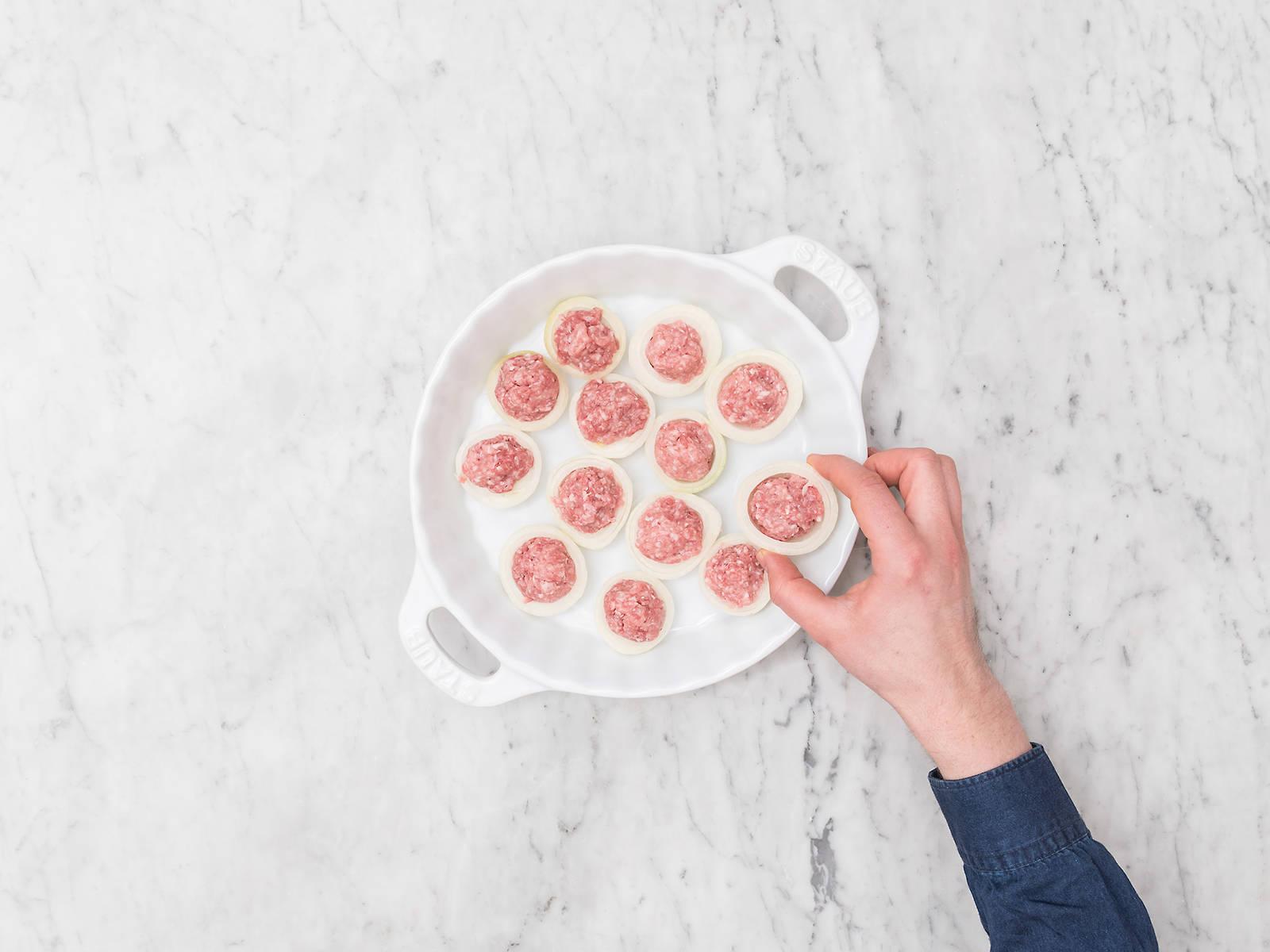Backofen auf 180°C vorheizen. Zwiebeln schälen, halbieren und die inneren Zwiebelschichten entfernen, um Platz für das Hackfleisch zu schaffen. Das Hackfleisch mit den Händen zu walnussgroßen Bällchen formen und jedes Bällchen in eine halbe Zwiebel legen. In eine Auflaufform legen und ca. 35 Min. backen, bis die Hackbällchen gebräunt sind.