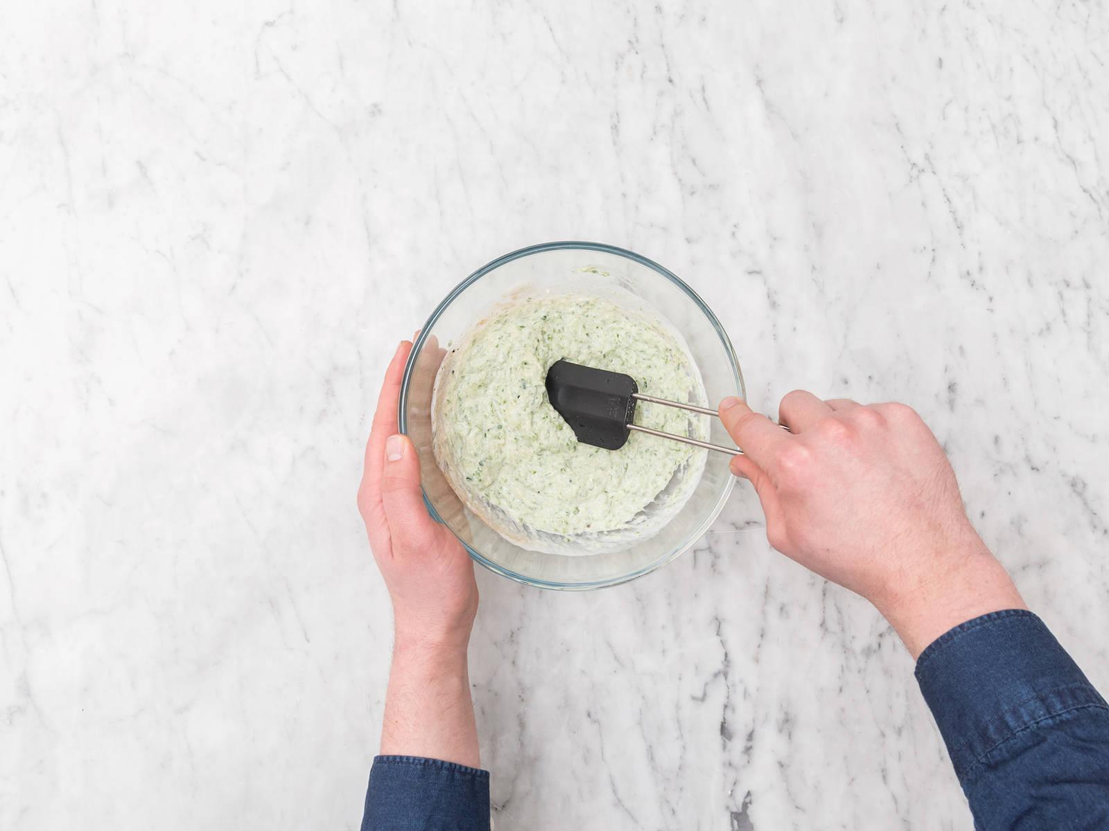 Gurken und Ingwer in ein Sieb reiben. Sieb über einer Schüssel platzieren und so viel Flüssigkeit wie möglich mit einem Gummispatel aus der Gurken-Ingwer-Mischung ausdrücken. Flüssigkeit weggießen und die geriebenen Gurken und Ingwer in eine saubere Schüssel geben. Joghurt und gemahlenen Kreuzkümmel dazugeben. Mit Salz und Pfeffer abschmecken und vermengen.
