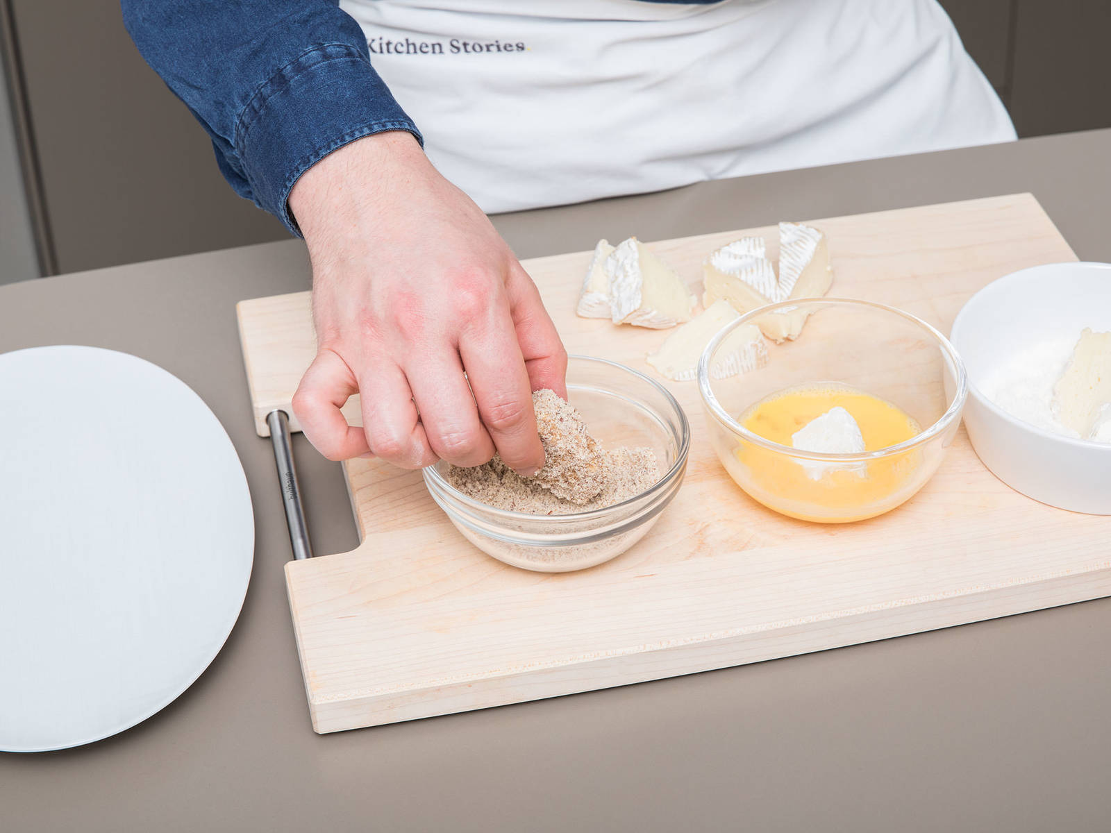 Add ground hazelnuts and breadcrumbs to a small bowl and stir to combine. Whisk egg in a second bowl and add flour to a third one. Cut camembert into equal-sized pieces and coat each piece first in flour, then dredge in egg and finally coat in hazelnut-breadcrumbs mixture.