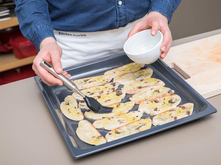 将拖鞋面包切成薄片,放到铺好烘焙纸的烤盘上。在面包两面都刷上剩余的橄榄油,放入烤箱,以180℃烤10分钟,或直至面包片变成金棕色且质地焦脆。