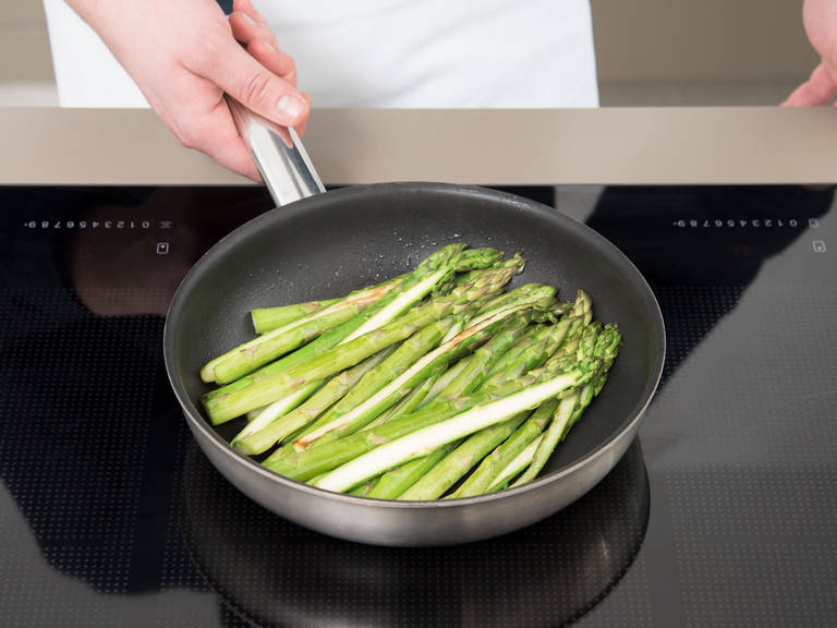 将烤箱预热至180度。在煎锅中,中高火加热橄榄油。放入芦笋条,煎5分钟,或直至芦笋稍微变软但仍脆口。