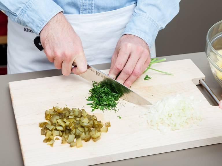 Abgekühlte Kartoffeln schälen und in dünne Scheiben schneiden. Die Kartoffelscheiben in eine Schüssel geben. Gewürzgurken und Zwiebeln fein würfeln. Petersilie und Dill fein hacken. Beiseitestellen.