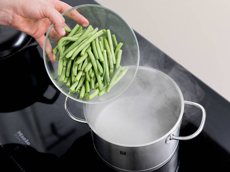Bring a pot of water to a boil and salt generously. Trim ends of green beans and cook in boiling water for approx. 5 min. Transfer to a large bowl filled with ice or cold water to stop the cooking process and preserve the bright green color. Dice the smoked bacon and chop the summer savory.
