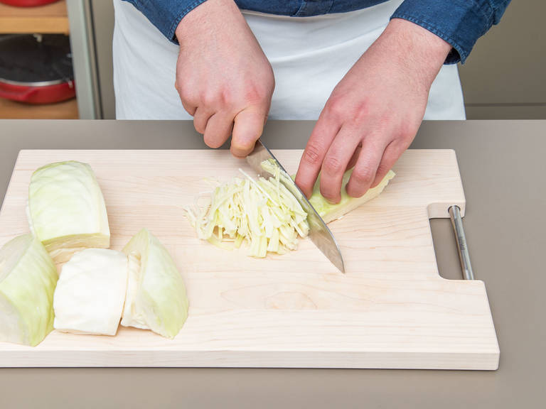 Clean and quarter white cabbage. Make a cut to remove the stem. Slice the white cabbage thin and add to a large bowl.