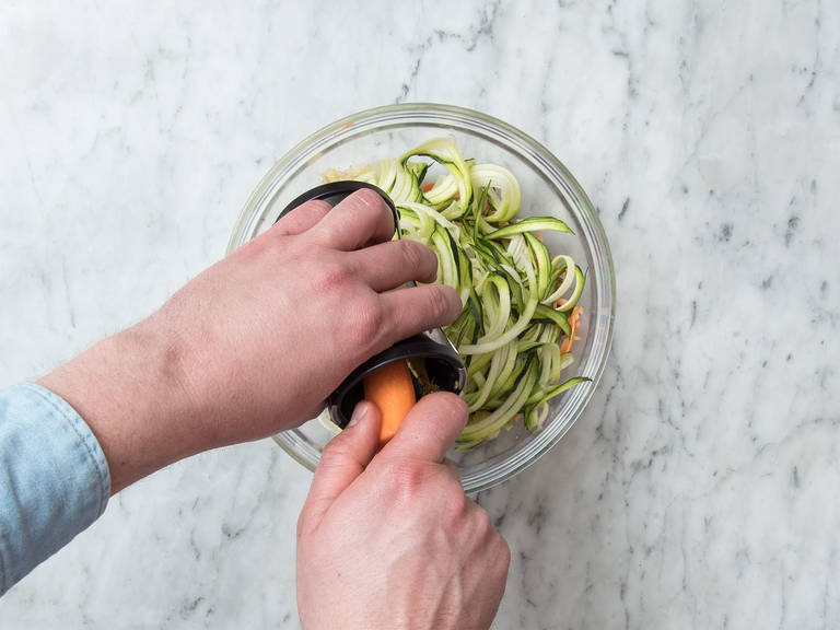 Using a vegetable spiralizer, cut sweet potatoes, carrots, beetroot, and zucchini into spaghetti-like noodles. Add to a large bowl and season with salt and sugar. Let sit for approx. 5 min.