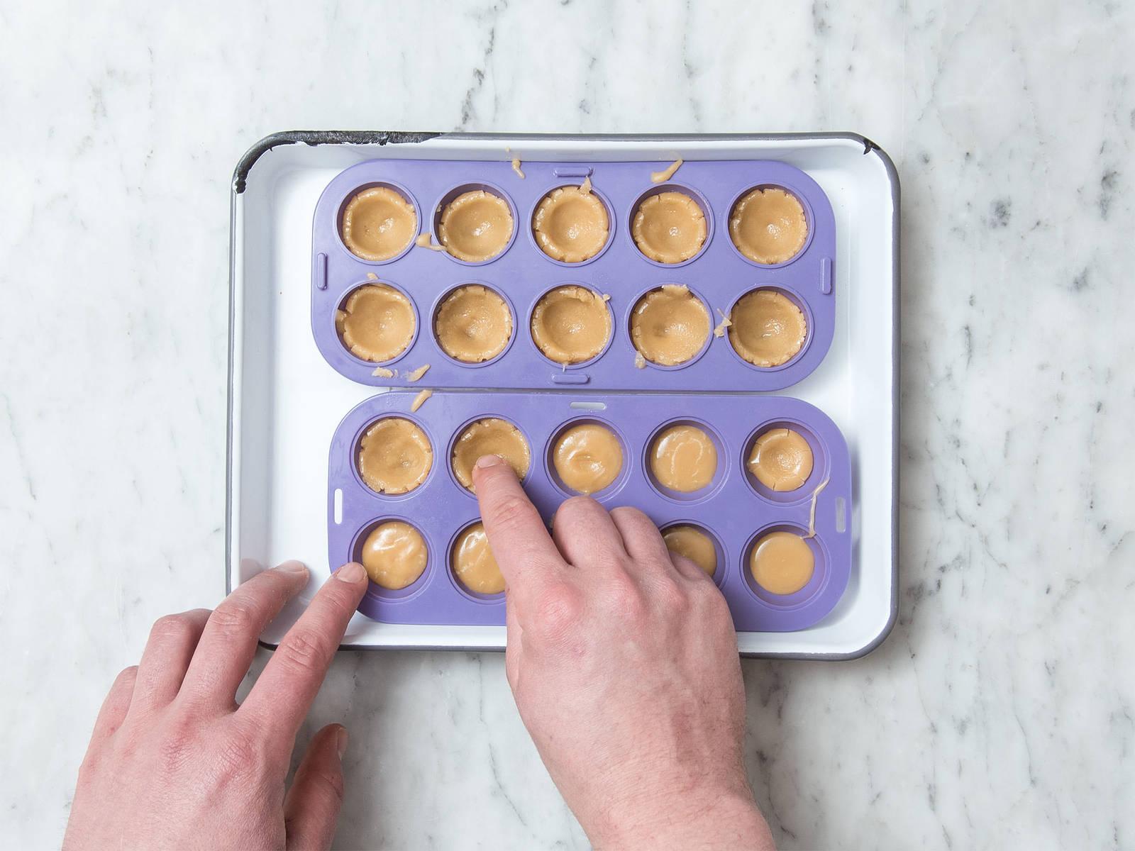 Silikonformen bis zur Hälfte mit Karamell füllen und ca. 10 Min. in den Kühlschrank stellen. Das Karamell sollte noch immer formbar sein. Karamell mit den Fingern an den Rändern der Silikonformen hochdrücken, um kleine Schälchen zu formen. In jedes Schälchen eine Haselnuss legen.