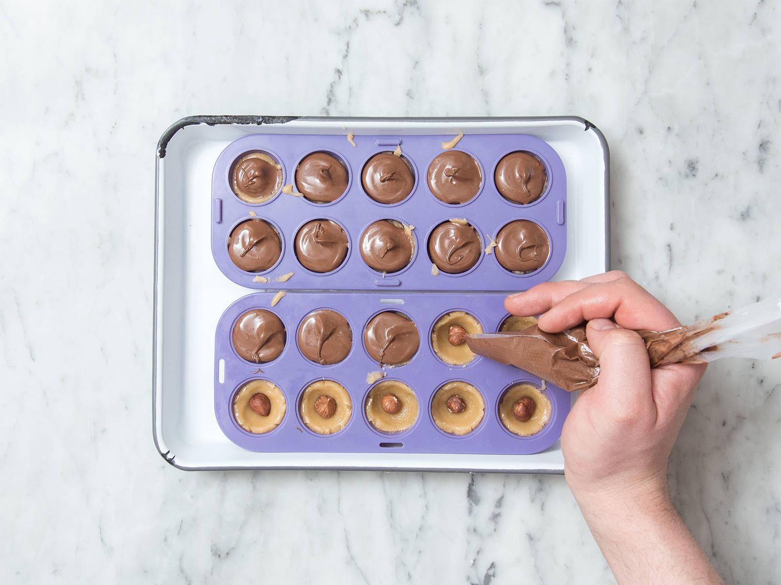 Nuss-Nougat-Creme in einer hitzebeständigen Schüssel über einem Topf mit köchelndem Wasser schmelzen lassen. Geschmolzene Creme in einen Spritzbeutel füllen und die Spitze des Beutels abschneiden. Die Karamellschälchen mit der Creme füllen, bis die Haselnüsse bedeckt sind. Die Formen mehrmals auf die Arbeitsfläche klopfen, um Luftblasen entweichen zu lassen. Ca. 45 Min. im Kühlschrank ruhen lassen, oder bis die Creme fest ist.