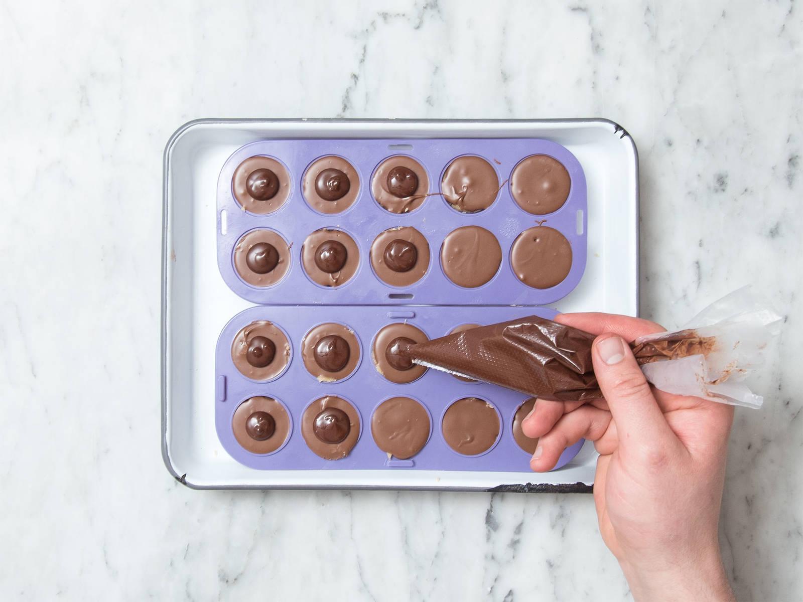 Zartbitterschokolade hacken und drei Viertel der Schokolade in eine hitzebeständige Schüssel geben. Über einem Topf mit köchelndem Wasser schmelzen lassen. Vom Herd nehmen und die restliche gehackte Schokolade unterrühren. Geschmolzene Schokolade in einen zweiten Spritzbeutel füllen und die Spitze des Beutels abschneiden. Kleine Schokoladenkreise auf die feste Nuss-Nougat-Creme geben und ca. 25 Min. trocknen lassen. Anschließend aus der Form nehmen und genießen!