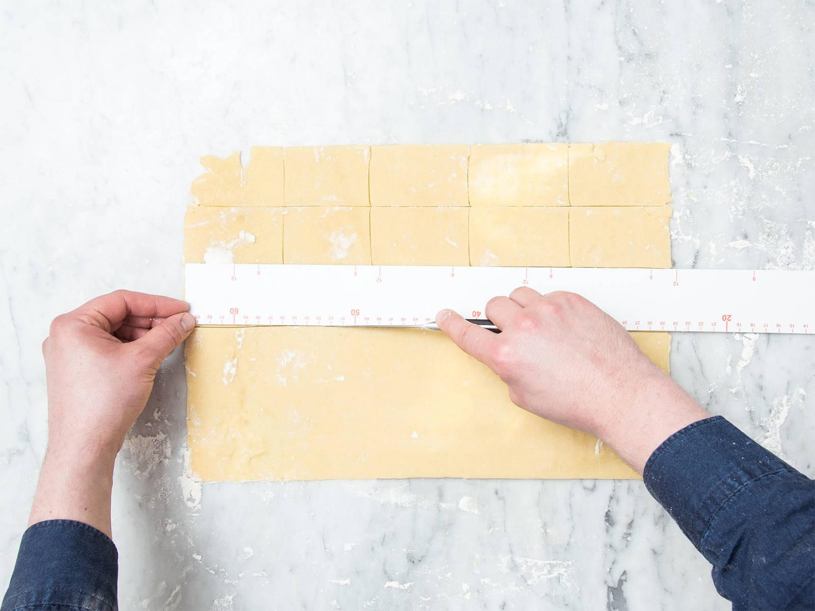 Den Teig auf einer bemehlte Arbeitsfläche ausrollen, bis er ca. 3-mm dick ist. Die Ränder mit einem Messer gerade schneiden und den Teig in 5x8-cm große Rechtecke schneiden. Die Hälfte der Teigstücke auf ein mit Backpapier ausgelegtes Backblech legen.