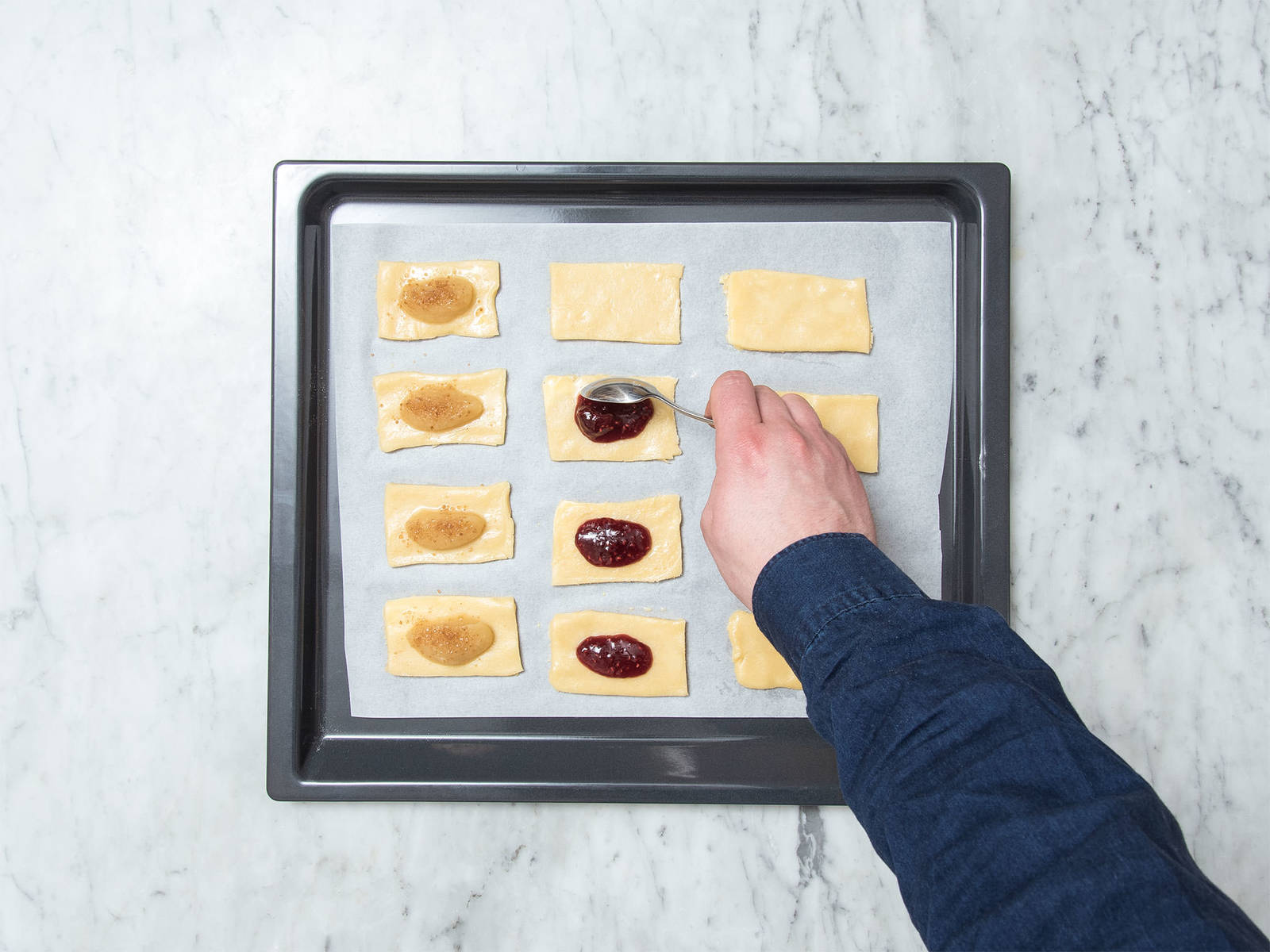 Die Teigrechtecke auf dem Backblech mit der Ei-Milch-Mischung bestreichen. Auf einem Drittel Apfelmus verteilen und mit Zimt-Zucker-Mischung bestreuen. Auf ein weiteres Drittel teelöffelweise Marmeladen-Füllung und auf die restlichen Teigrechtecke Nutella in die Mitte geben. Dabei immer etwas Abstand zu den Rändern lassen.