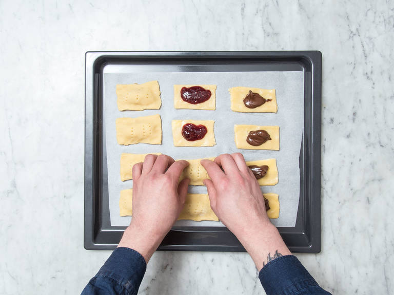 Use a fork to poke holes in the remaining half of the dough, then transfer them onto the filled dough rectangles on the baking sheet. Use your fingertips to press around the filling, then use a fork to seal the edges so the filling will stay inside. Preheat oven to 175°C/350°F and refrigerate pop tarts for approx. 20 min. Afterwards, bake them for approx. 20 min. until golden brown. Let cool.