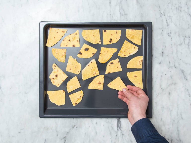 Preheat the oven to 200°C/390°F. Cut the tortilla chip circles into triangles. Place the triangles onto a baking sheet and bake for approx. 5 min.