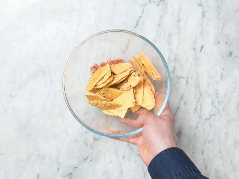 Die gebackenen Nachos, Paprikapulver und Salz in eine großen Schüssel geben und schwenken.