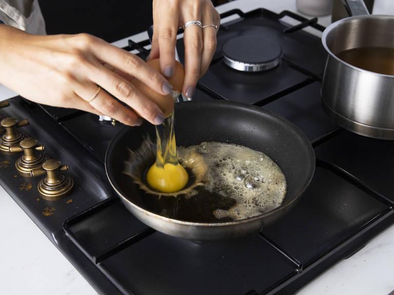 大略剁碎培根,剁碎香葱。将鸡肉高汤倒入一个锅中,中低火加热。用些许黄油煎鸡蛋两面,但不要让蛋黄焦固。撒盐与胡椒调味,置于一旁待用。