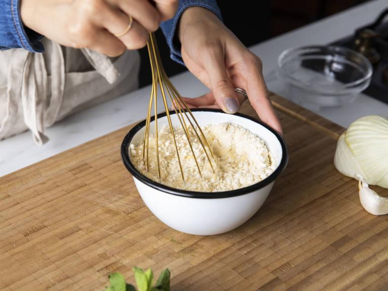 将鹰嘴豆粉、水和三分之一的橄榄油混合到一起,撒盐与胡椒调味,置于一旁。