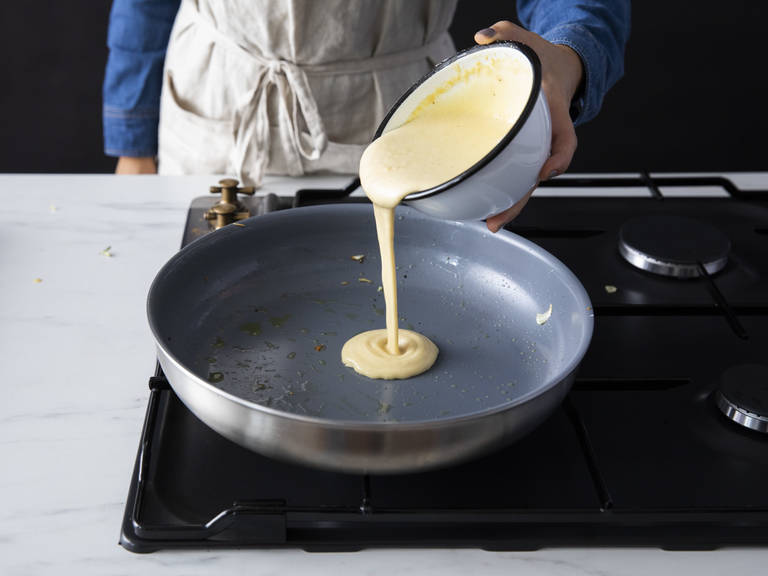 在同一个锅中,倒入剩余的些许橄榄油和半份鹰嘴豆面糊。煎5分钟,然后翻面再煎5分钟。铲出煎饼,倒入更多橄榄油,再煎剩余的半份面糊。