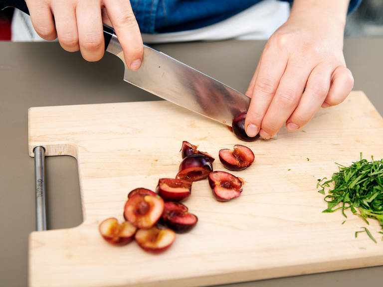 Using a knife, halve cherries and remove the pit. Pluck basil leaves from stems, thinly slice, and set aside until serving.