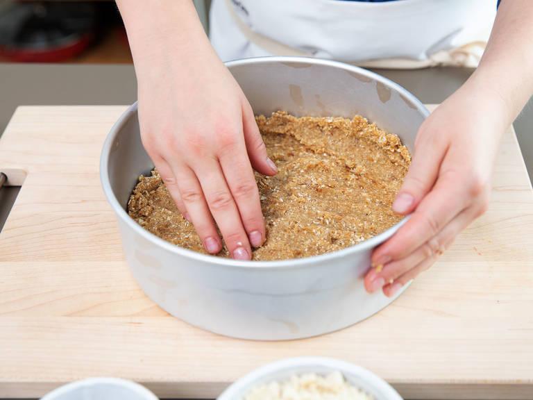Die Dattel-Mandel-Mischung in einer Backform oder Springform verteilen und fest andrücken. Nun gemahlene Mandeln, Ahornsirup und Salz in einen Zerkleinerer geben. Zu einer glatten Masse vermixen und auf dem Dattel-Mandel-Boden verstreichen.