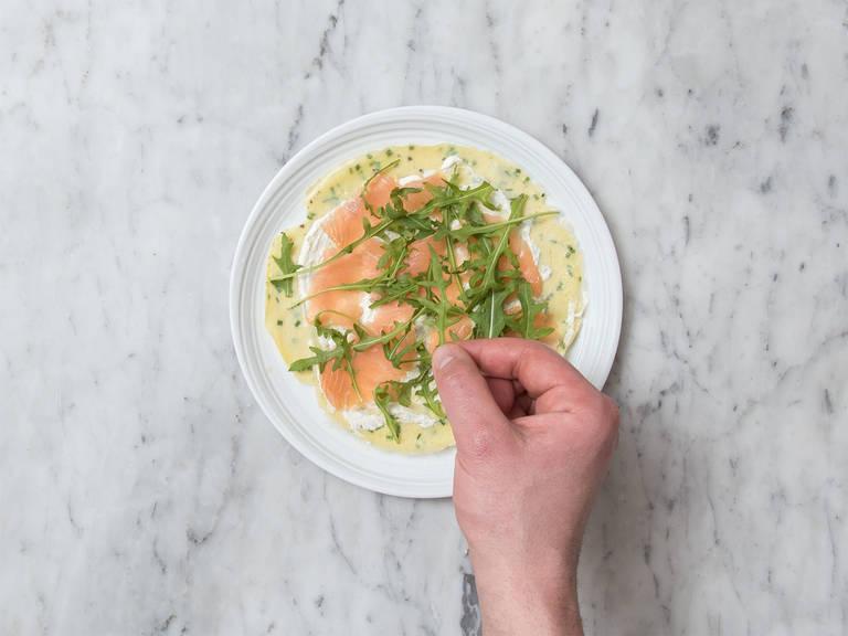 在每片煎蛋饼上都抹上些许奶油奶酪混合物,然后放上烟熏三文鱼和芝麻菜,小心地将蛋饼卷起,斜切成两半,立即享用吧!
