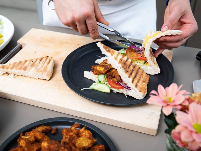 Für den Salat Gurke halbieren und in Scheiben schneiden, Tomaten und rote Zwiebel fein schneiden, Eisbergsalat in Streifen schneiden und eingelegte Chili ebenfalls klein schneiden. Um das Sandwich zu belegen, Mangosoße im Brot verstreichen, mit Salat füllen und die Hähnchenbruststreifen daraufgeben. Guten Appetit!