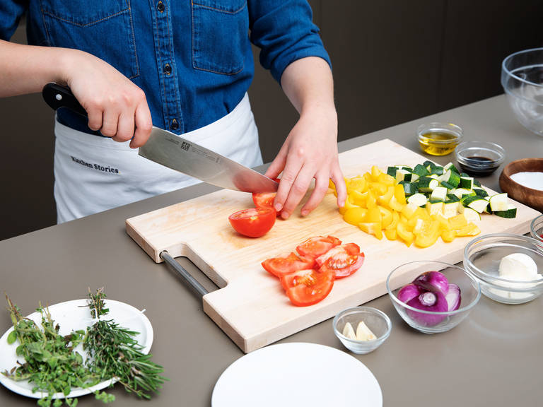 Preheat the oven to 200°C/390°F. Quarter the eggplant and dice into large chunks. Transfer to a sieve set over a bowl, salt well, and massage. Let drain for approx. 10 min. In the meantime, dice zucchini and yellow bell pepper. Slice tomatoes lengthwise into chunks. Finely dice red onion and garlic. Finely chop marjoram and oregano. Using kitchen twine, tie rosemary and thyme to into a small bouquet garni.