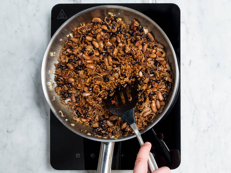 Preheat the oven to 180°C/370°F. Peel and dice onion. Drain and rinse canned beans. In a frying pan, heat olive oil and sauté diced onion. Add ground beef and fry for approx. 1 – 2 min. Add chili powder, paprika powder, ground cumin, Cayenne pepper, dried oregano, and sugar and season with pepper and salt. Mix well and fry for another 2 – 3 min. Stir in pinto beans, black beans, and tomato paste, then remove frying pan from heat.